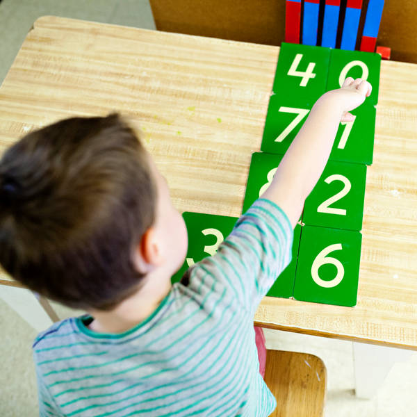 child arranging cards with numbers