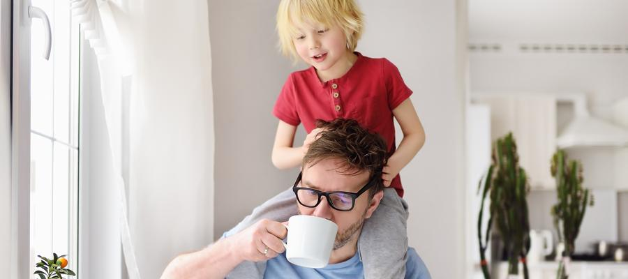 child on parent shoulder while drinking coffee