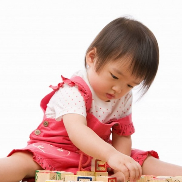 special need girl playing with wooden blocks