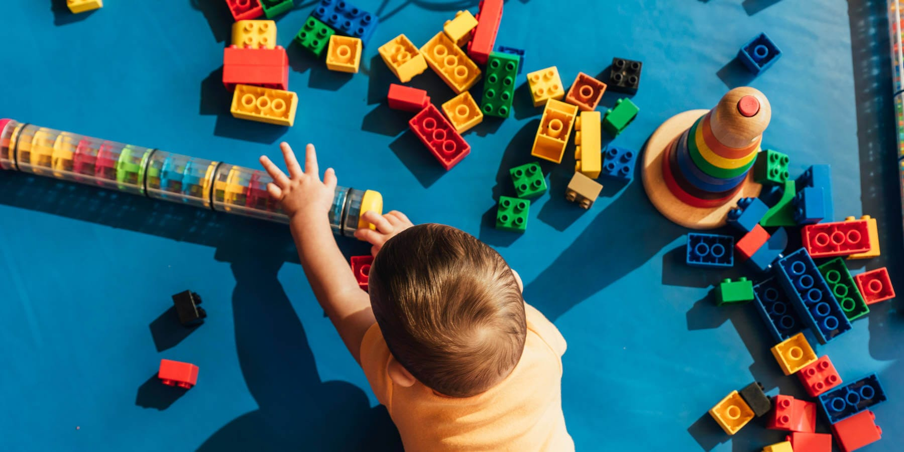 happy toddler playing with lego blocks